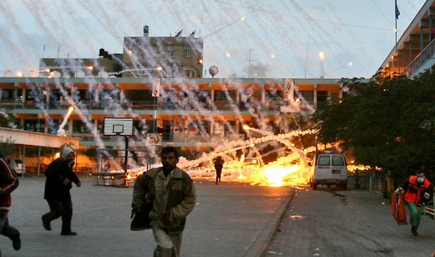 Palestinian civilians and medics run to safety during an Israeli strike over a UN school in Beit Lahia, northern Gaza Strip early on January 17, 2009 . (AFP)
